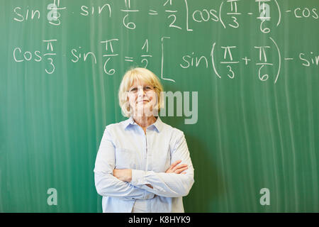 Senior woman as math teacher or lecturer in front of chalkboard - Stock Photo