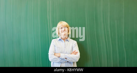 Senior woman as lecturer or teacher in front of chalkboard - Stock Photo