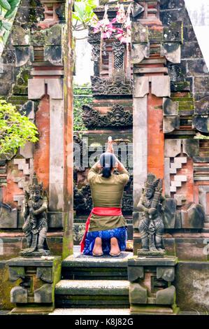 Indonesia. Bali. Ubud. Balinese woman praying in a temple - Stock Photo