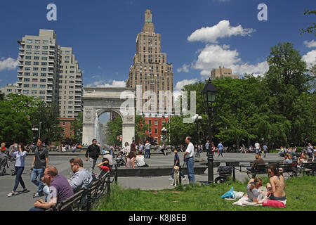 New York, NY, USA - June 1, 2017: Tourists and New York locals alike enjoy a sunny day in Washington Square Park - Stock Photo