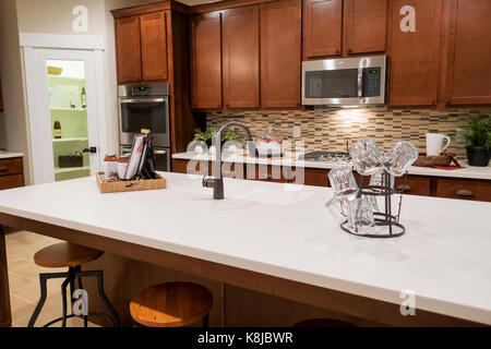 A kitchen with brown cabinets and an island with a stove, microwave, sink and a pantry. - Stock Photo