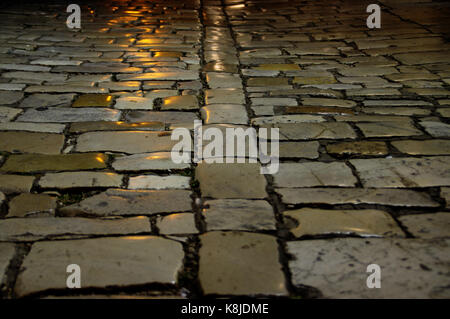 Vintage paving stone road. Perspective view of cobbled street. - Stock Photo
