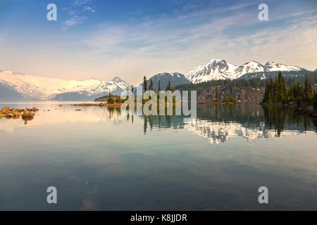 Hazy Garibaldi Lake Landscape with distant snowy mountain tops obscured from summer wildfire smoke in Coast Mountains - Stock Photo