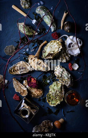 Seafood feast with oysters and wine, arranged on dark blue background. Above view, flat lay. - Stock Photo