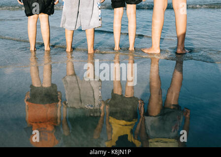 reflection of kids standing at the beach in the evening.travel and family concept,friendship and togetherness concept - Stock Photo