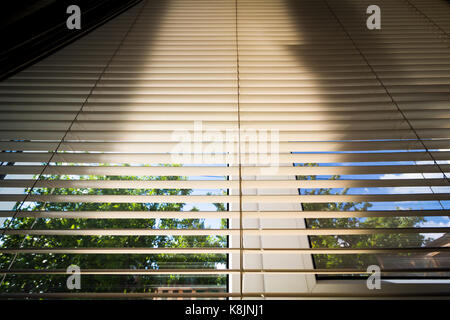 The summer sun shines through the blinds of the window of a rural house. - Stock Photo