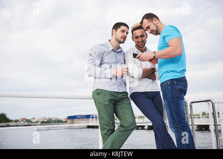 A group of young and happy men on the pier. - Stock Photo