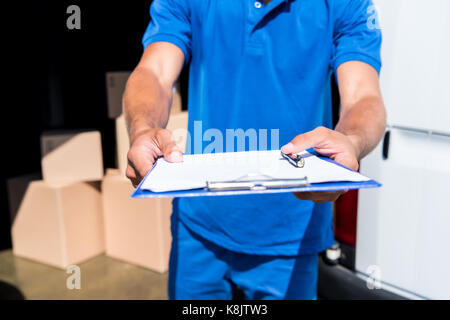 delivery man with clipboard - Stock Photo