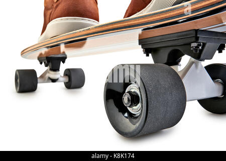 Dynamic rear view of a Black and wooden skate board and brown leathers shoes isolated on a white background with - Stock Photo