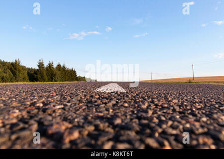 photographed the new asphalt road. photo taken from below and see the small stones and tar stains. Blue sky and - Stock Photo