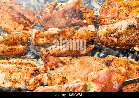 photographed close-up of orange succulent kebabs of pork during their cooking on the fire. Small depth of field. - Stock Photo