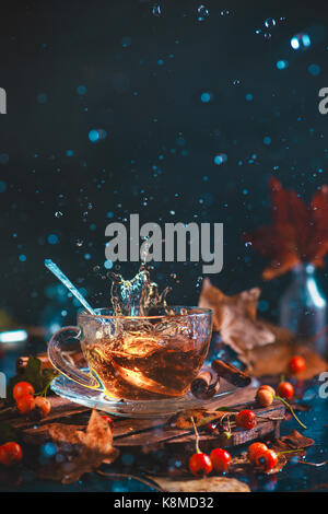 Action autumn still life with tea cup, wooden coaster, autumn leaves and berries, teaspoon and a frozen in motion - Stock Photo