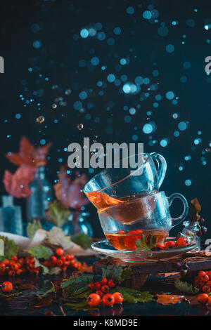 Dark autumn still life with a pair of teacups, leaves, berries and cinnamon on a wet background. Action photography - Stock Photo