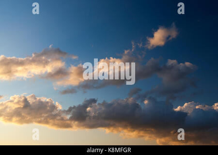 clouds of white and gray colors on a blue sky in sunlight. - Stock Photo