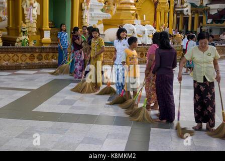 Cleaning the floor at Shwedagon Pagoda, Yangon, Burma, Myanmar, Southeast Asia - Stock Photo
