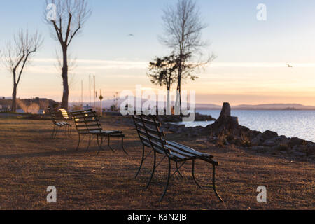 Sitting benches on a lake shore at sunset - Stock Photo