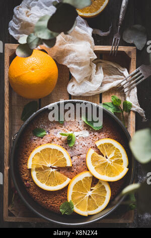 Orange cake decorated with orange slices and mint leaf on wooden tray. Top view. Food still life - Stock Photo