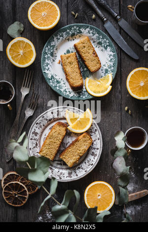Orange cake served on vintage plates on rustic wooden table background. Food still life. Top view, vertical composition - Stock Photo