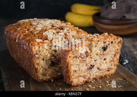 Homemade banana bread loaf with walnuts sliced on wooden cutting board. Closeup view, horizontal - Stock Photo
