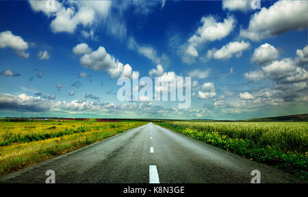 image of wide open prairie with a paved highway stretching out as far as the eye can see with beautiful small green - Stock Photo