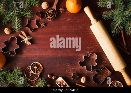Winter holidays Christmas New Year background with cookie cutters, spices, nuts, Christmas tree and Gingerbread - Stock Photo
