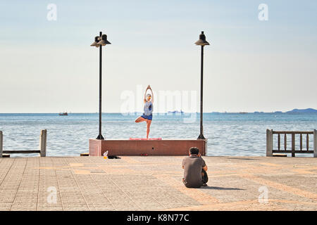 Photographer with model working outdoors. Photographer shooting outside. On location. Yoga vrksasana tree pose - Stock Photo