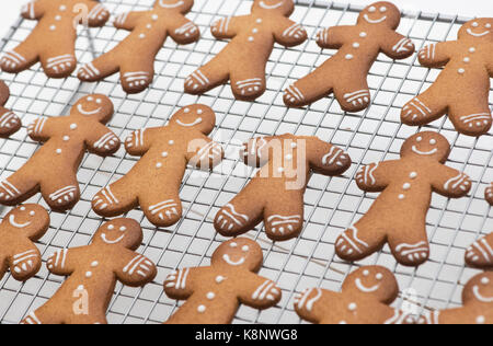 Gingerbread Men biscuits on a wire cooling rack. One where the head has been eaten - Stock Photo