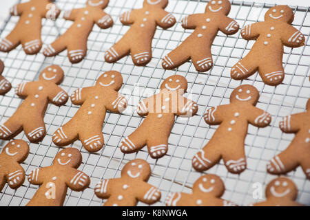 Gingerbread Men biscuits on a wire cooling rack - Stock Photo