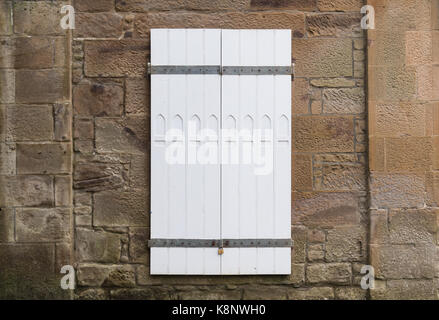 White Painted Panel Doors with a window design and closed with a gulvanised padlock and bars. Plenty of room for text to be added to the image at both Stock Photo