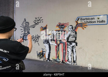 London, UK.  20 September 2017. A tourist photographs a new artwork outside the Barbican Art Gallery by street artist - Stock Photo