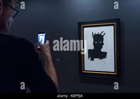 London, UK.  20 September 2017.  A visitor photographs 'Self-Portrait', 1983, by Jean-Michel Basquiat.  Preview - Stock Photo