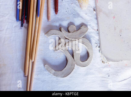 Symbol OM with clay on the desk. - Stock Photo