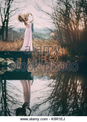 Reflections of Beauty. A girl in a pink dress standing by a pond. Her reflection below - Stock Photo