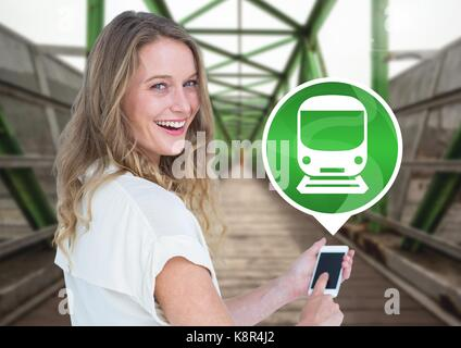 Digital composite of Woman holding phone with train icon on railway track - Stock Photo