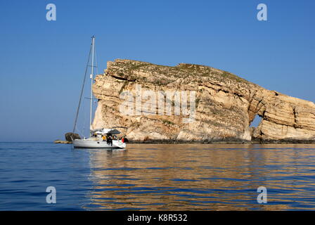 Sailing yacht anchored in front of Fungus rock, Dwejra bay, San Lawrenz, Gozo, Maltese archipelago - Stock Photo