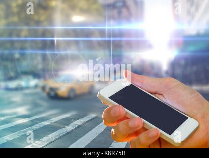 Digital composite of Hand holding phone in city - Stock Photo