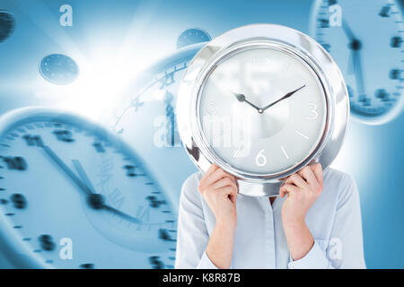 Businesswoman in suit holding a clock against digital composite image of wall clocks - Stock Photo