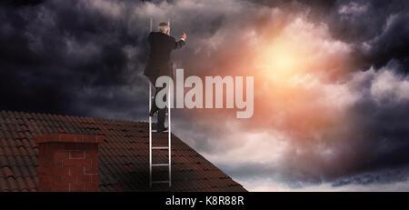 Mature businessman climbing career ladder  against gloomy sky - Stock Photo