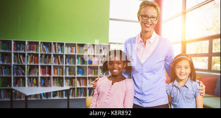Portrait of happy teacher with students against school library - Stock Photo