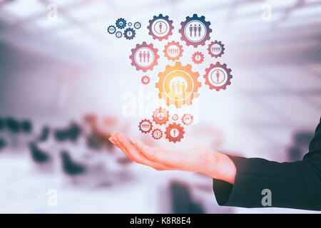 Businesswomans arm presenting against computers in office - Stock Photo