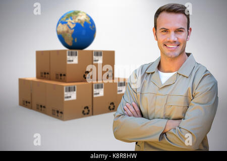 Confident delivery man standing with arms crossed against grey background - Stock Photo