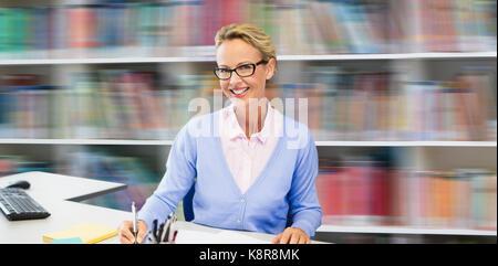 Portrait of teacher writing on book against shelf of books - Stock Photo