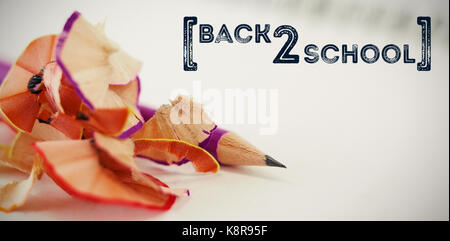 Back to school text over white background against close-up of pencil with shavings - Stock Photo