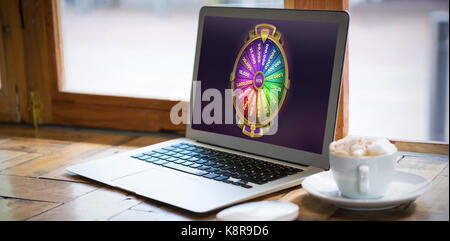 Colorful wheel of fortune on mobile screen against laptop by coffee cup on table in cafe - Stock Photo