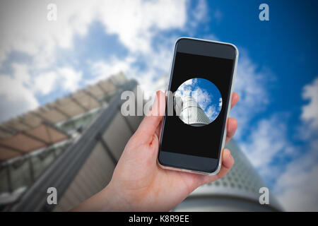 Hand holding mobile phone against white background against low angle view of skyscraper - Stock Photo
