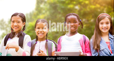 Portrait of friends with digital tablets against trees in the forest - Stock Photo