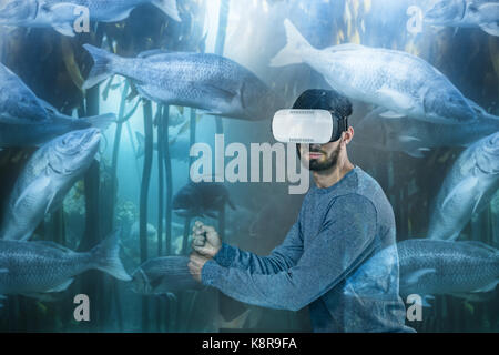 Big fish swimming in a tank  against man with blue sweet playing vr - Stock Photo