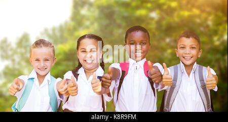 Portrait of students showing thumbs up sign against trees in the forest - Stock Photo