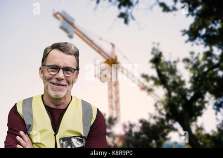 Portrait of senior worker wit arms crossed wearing reflective clothing against view of a crane - Stock Photo