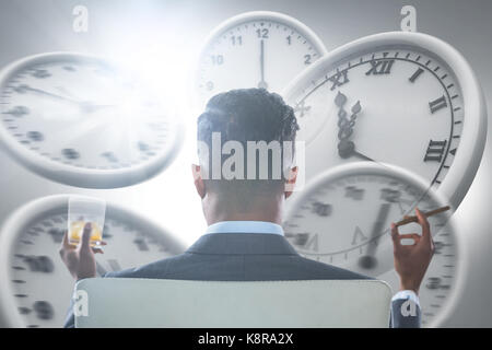 Rear view of businessman holding whisky glass and cigar against computer graphic image of wall clocks - Stock Photo